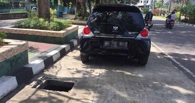 Lobang besar di badan jalan membahayakan pengendara. Manhole hilang dicuri.