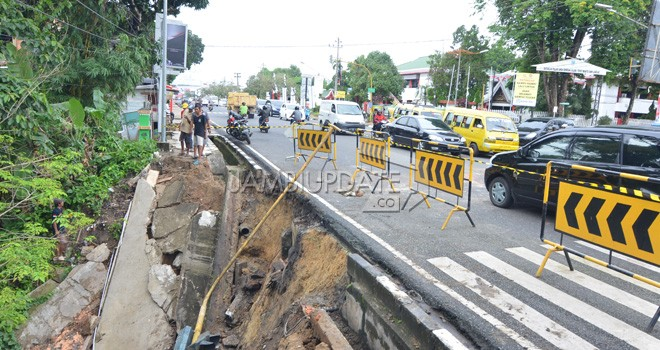 Jalan longsor di kawasan TAC Kota Jambi sudah tiga bulan dibiarkan. Belum ada tanda-tanda perbaikan.