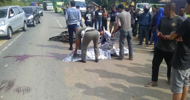 Pihak kepolisian dibantu oleh warga saat mengevakuasi korban di tengah jalan usai terjadinya kecelakaan, Rabu (8/8).