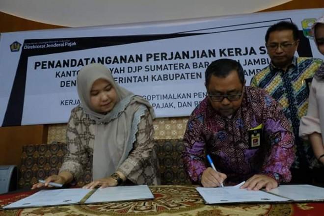 Bupati Masnah saat menandatangani MoU bersama Kakanwil DJP Sumbar-Jambi Ain Nursalim Saleh.