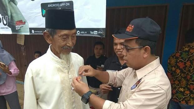 PEMILIH : Komisioner KPU Provinsi Jambi, M. Sanusi memasangkan pin GMHP kepada salah satu warga Tanjabtim pada segerak cek pemilih serentak, Rabu (17/10) kemarin.