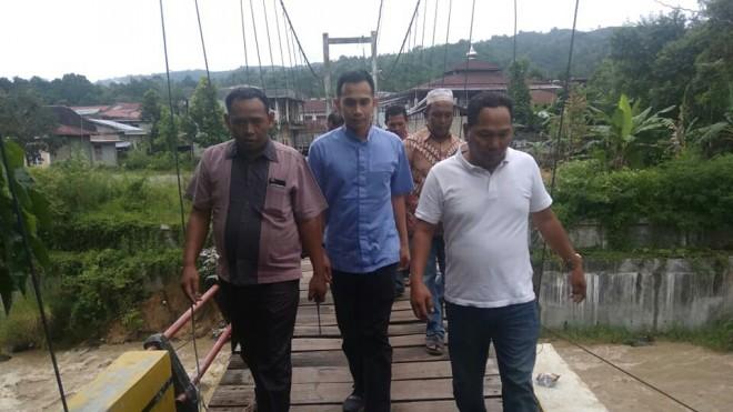FOTO : IST/JE BLUSUKAN : Calon anggota DPR RI Dipo Nurhadi Ilham harus melewati jembatan untuk mengunjungi, berdialog serta menyerap aspirasi masyarakat.