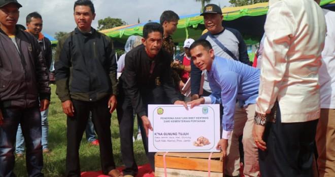 Staf khusus pimpinan DPR RI, Dipo Nurhadi Ilham menyerahkan bantuan bibit kentang dari untuk petani Kayu Aro. Foto : Ist