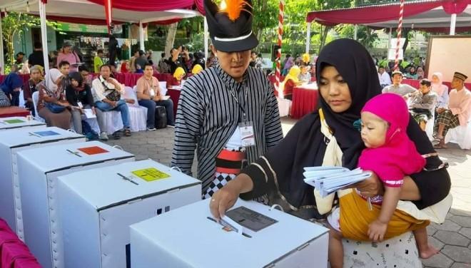 Salah satu petugas KPPS memastikan seorang ibu memasukkan surat suara di kotak yang benar pada simulasi nasional Pemilu 2019.