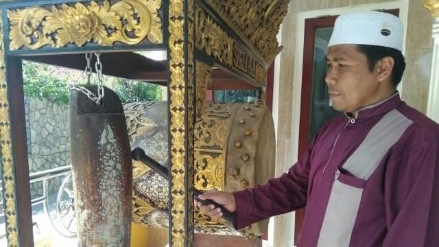 Ibrahim tengah memukul bedug tanda memasuki waktu salat. (Alwi Alim/ JawaPos.com)