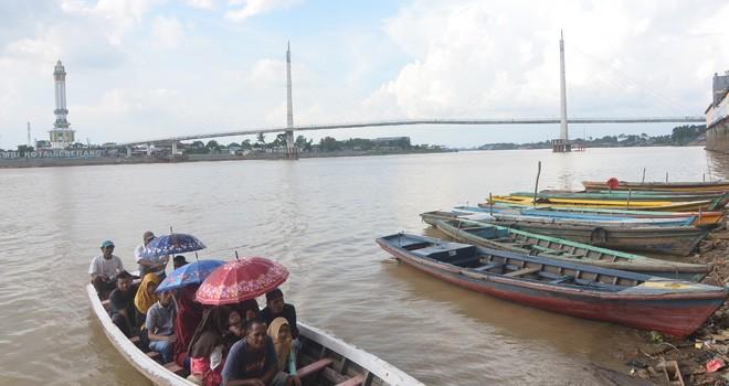 Penumpang perahu ketek menggunakan payung karana teriknya matahari (26/5). Informasi BMKG Stasiun Jambi, Jambi mulai memasuki musim kemarau.