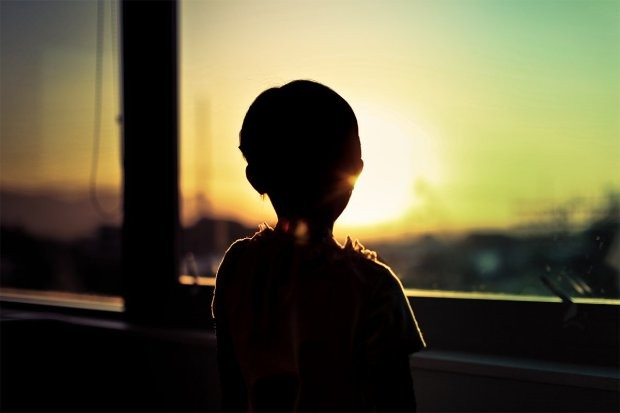 Silhouette of child by window looking at sunset.