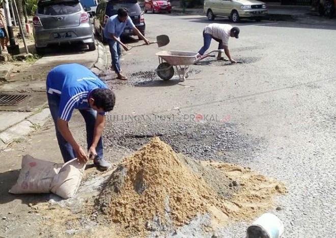Warga berinisiatif menambal jalan yang rusak.