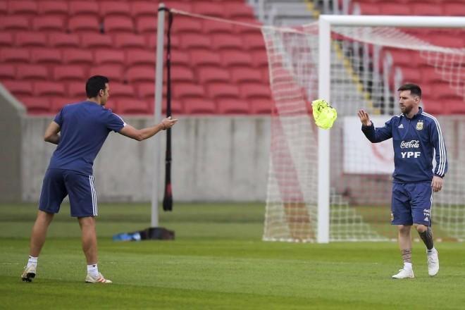 Pelatih Argentina, Lionel Scaloni melemparkan rompi kepada Lionel Messi. (Foto: Carl DE SOUZA / AFP)