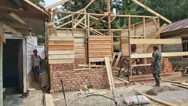 Babinsa Koramil 415-14/Muara Bulian, Sersan Satu Bambang Sutomo gotong royong bersama warga sekitar membangun rumah Juriani RT 06 Desa Ladang Peris.