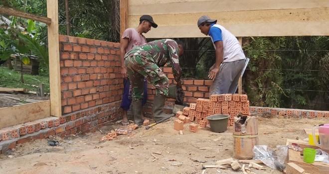 Sertu Bambag Sutomo Babinsa Koramil 415-04/MB membantu warga gotong royong memasang batu-bata dinding rumah milik Marlan RT 05, Desa Ladang Peris, Kecamatan Bajubang, Kabupaten Batanghari.