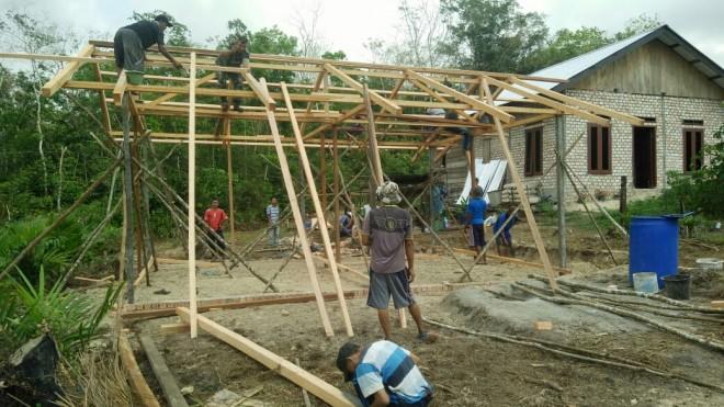 Sersan Dua (Serda) Alfian membantu warga RT 08 Desa Ladang Peris.