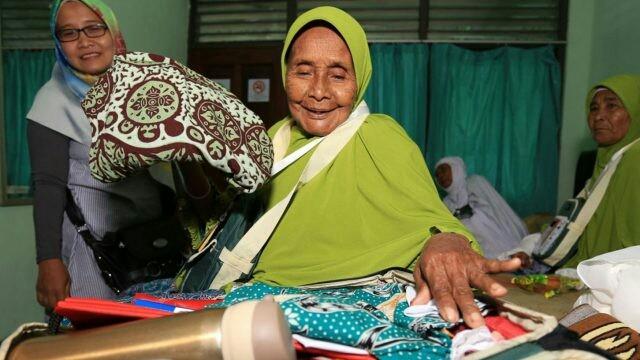 Tiwa binti Sajirun sedang menata barang-barang di tas tentengnya. Dia merupakan jamaah tertua dengan usia 103 tahun. (Robertus Risky/Jawa Pos)