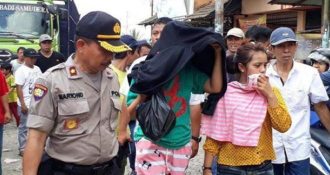 Ina (30) dan Ica terlihat salah tingkah ketika didatangi petugas Satreskoba Polresta Samarinda di salah satu rumah di Gang Tempurung III, Samarinda Ulu, Kalimantan Timur, Rabu (17/7).
