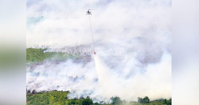 M RIDWAN/JE WATER BOMBING: Salah satu helikopter melakukan pemadaman api di kawasan Desa Desa  Sipin Teluk Duren, Kecamatan Kumpeh Ulu kemarin (8/9). Kawasan ini menjadi kawasan terparah Karhutla sepanjang 2019 ini
