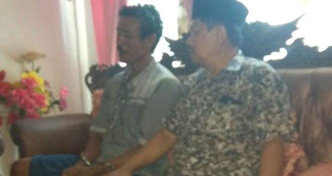 Hamzah (diborgol) saat diamankan di rumah Kades Simbur Naik, yang dijaga ketat oleh pihak Kepolisian.