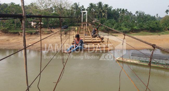 Warga sedang melakukan perbaikan jembatan gantung di Dusun Teluk Pandak, Bungo kemarin (8/10).