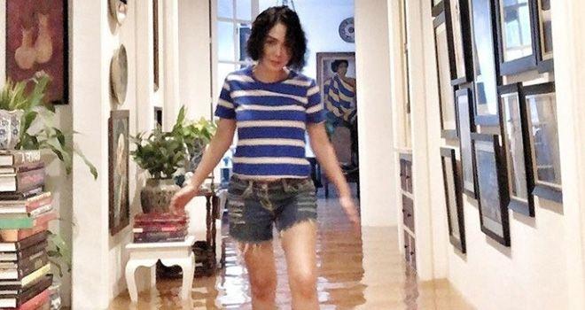 Yuni Shara di dalam rumahnya yang terkena banjir.