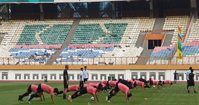 Timnas Indonesia U-19 yang sedang seleksi menjalani latihan dengan latar tribun timur penonton di Stadion Wibawa Mukti yang rusak.