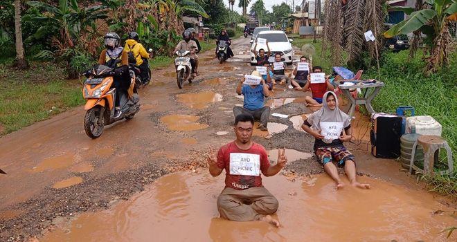 Sejumlah warga mengekspresikan bentuk kekecewaannya dengan menjadikan jalan rusak sebagai tempat berswafoto.