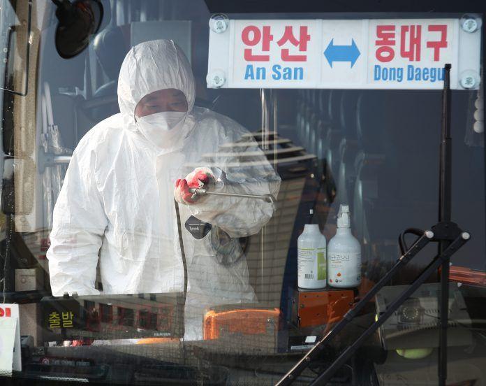 Seorang pekerja dari dinas kesehatan melakukan penyemprotan desinfektan di bus yang berangkat ke Daegu.