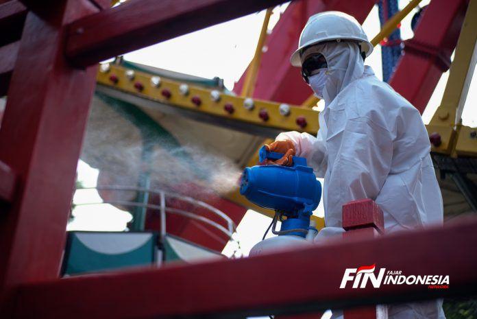 Petugas mengenakan pakaian pelindung penyemprotan disinfektan di area Dufan, Ancol, Jakarta, (14/3).Pembersihan sejumlah wahana di Dufan dengan menggunakan cairan disinfektan guna mengantisipasi penyebaran virus corona (Covid-19).