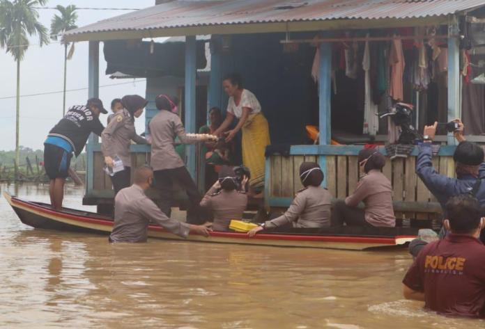 Personel Polres Muaro Jambi memberikan bantuan sembako untuk korban banjir di Pematang Jering, Muaro Jambi.