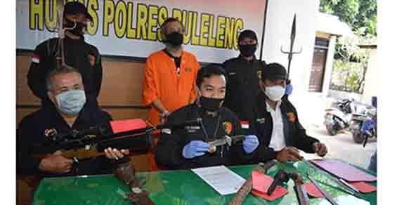 Tersangka Gusti Sudriyasa saat ditemui di Mapolres Buleleng, Senin (29/6) bersama sejumlah barang bukti berupa senjata tajam, senapan angin, dan pistol gas jenis organ.
