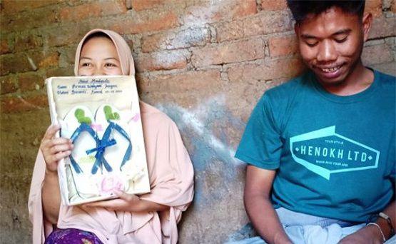 Helmi Susanti, memegang bingkai berisikan sandal jepit yang merupakan mahar pernikahannya dengan Iwan Firman Wahyudi.