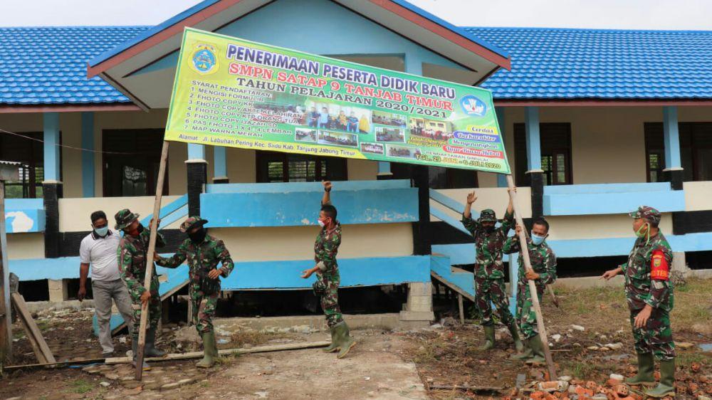Satgas TMMD Bantu Perbaiki Pemasangan Banner Penerimaan Siswa/i Baru di SMPN Satu Atap 9 Desa Labuhan Pering