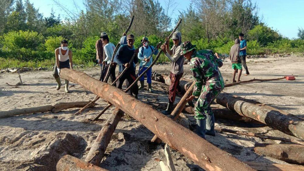 Satga TMMD Bersama Warga Desa Labuhan Pering Gotong royong Angkut Potongan Material yang Hanyut