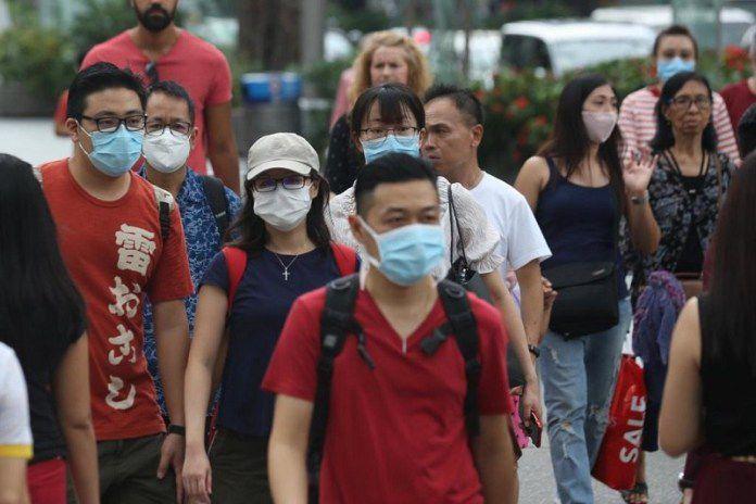 Sejumlah wisatawan mengenakan masker saat berada di ruang publik di Singapura sebagai upaya mencegah penularan corona.