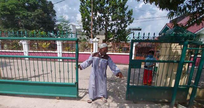 Sudarno bersama cucu laki-lakinya menunjukkan pintu pagar masjid.