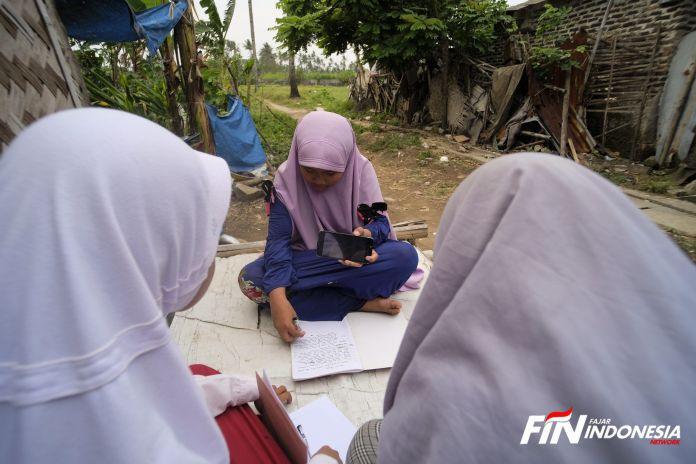 Tiga siswi melakukan belajar bersama di depan halaman rumah