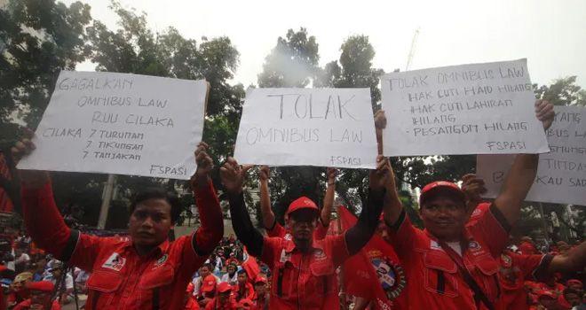 Massa yang tergabung dari Gerakan Buruh Jakarta menggelar aksi unjuk rasa menyerukan penolakan omnibus law di depan Gedung DPRD DKI Jakarta, Jakarta Pusat, (12/3).