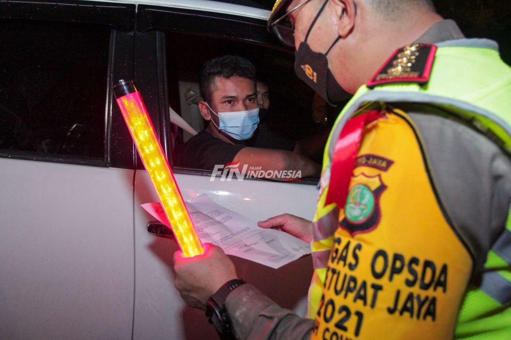 Petugas kepolisian memeriksa dokumen pengendara yang melintas dari arah Jakarta ingin menuju keluar Jakarta di Pintu Tol keluar Cikarang Barat, Kamis (6/05) dini hari. Pemeriksaan tersebut terkait larangan mudik lebaran 2021 yang dimulai dari tanggal 6 hingga 17 Mei sebagai upaya mengantisipasi risiko peningkatan kasus penularan COVID-19 jelang perayaan Hari Raya Idul Fitri 1442 H.