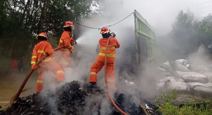 Petugas Damkar saat berusaha memadamkan api yang hampir menghanguskan satu unit truk pengangkut arang.